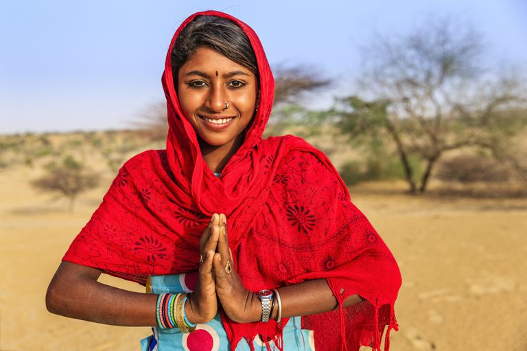 namaste--portrait-of-happy-indian-girl-in-desert-village--india-622457258-5a60ca9f7d4be80037c93e52