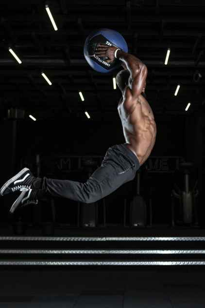 man jumping in mid air holding blue ball above his head