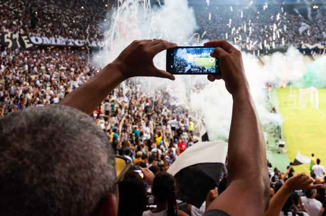 person taking photo of stage stadium presentation