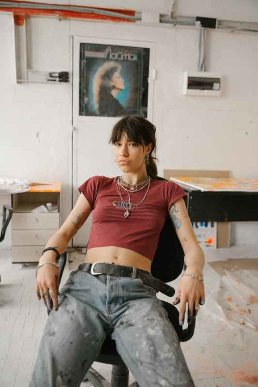 confident young woman sitting on office chair in old aged artist workshop